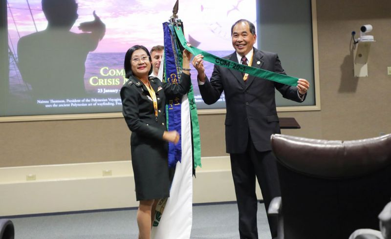 Sr. Col. Kanobsri Gesorn of Thailand and Director Gumataotao add the class streamer to the DKI APCSS flag.