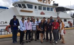 DKI APCSS Fellows visit Sector Honolulu, and discuss maritime response assets and capabilities, like the new Fast Response Cutters (FRC), pictured here with an FRC, the USCGC OLIVER BERRY.