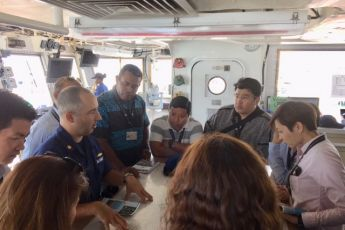 DKI APCSS Fellows discuss maritime crisis response challenges across the Main Hawaiian Islands while at the Chart Table onboard USCGC WALNUT's pilothouse